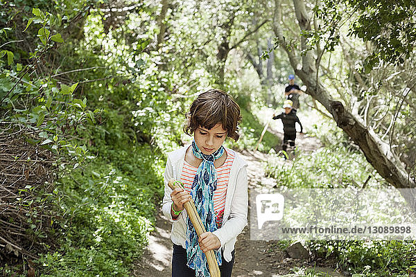 Girl holding stick while walking on footpath in forest