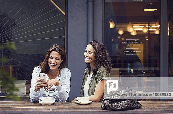 Glückliche Freundinnen mit Smartphone im Straßencafé