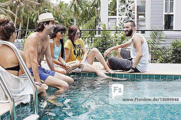 Glückliche Freunde sitzen am Pool