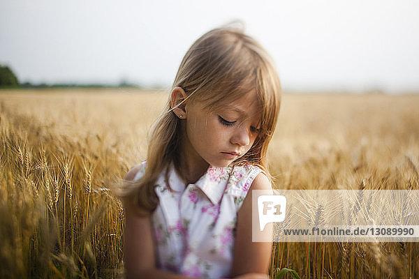 Upset girl standing against sky in farm