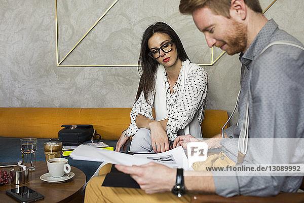 Geschäftskollegen beim Analysieren von Dokumenten in der Hotellobby