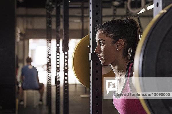 Determined female athlete lifting barbell in health club
