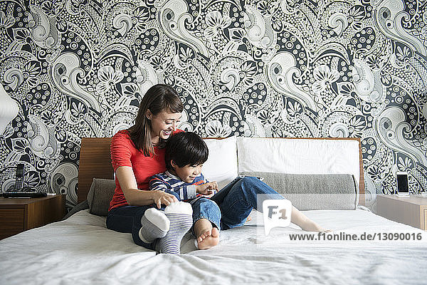 Mother and son smiling and using digital tablet while sitting on bed