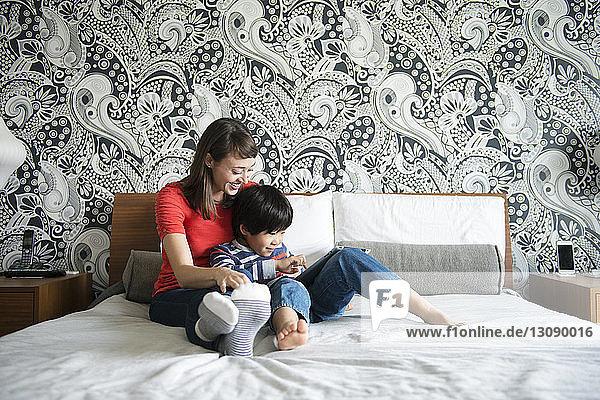 Mutter und Sohn lächeln und benutzen ein digitales Tablett  während sie auf dem Bett sitzen