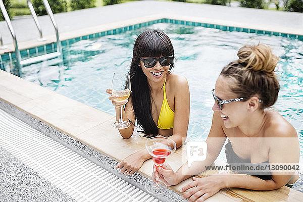 Fröhliche Frauen bei einem Drink im Schwimmbad
