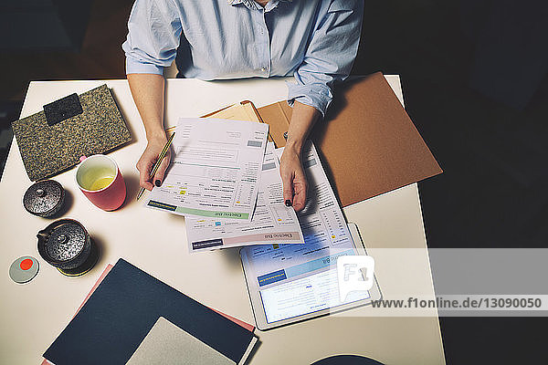 Midsection of businesswoman holding documents while sitting at desk in home office