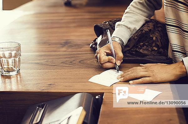Mitschnitt einer weiblichen Kundin  die eine Rechnung an der Kasse eines Cafés unterschreibt