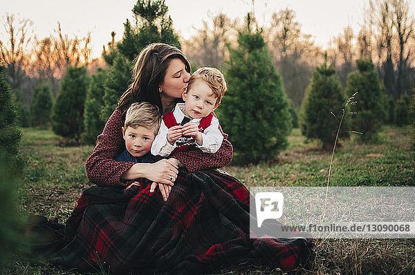 Mutter mit Söhnen sitzt bei Sonnenuntergang auf einem Feld im Wald