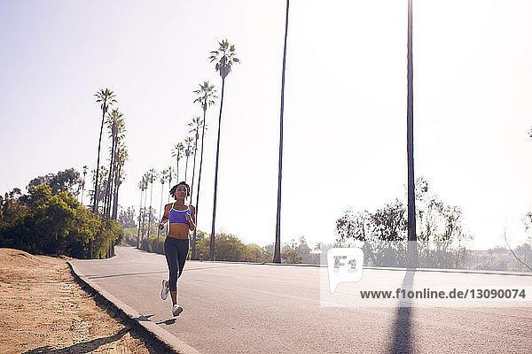 Junge Frau joggt an einem sonnigen Tag auf der Straße