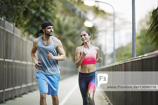 Front view of couple jogging on road