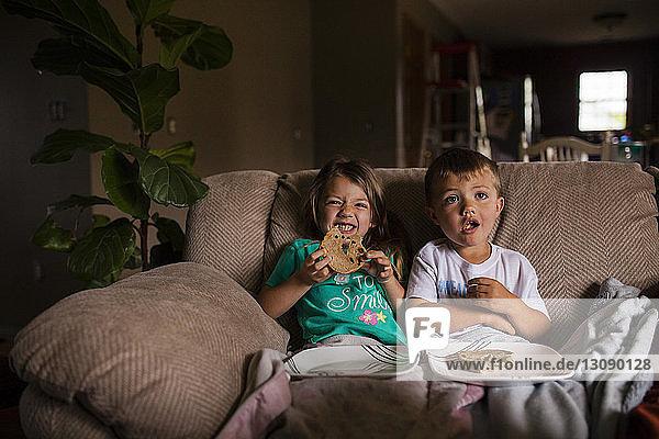 Happy siblings eating bread on sofa