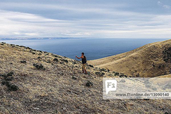 Wanderer besteigt Berg gegen Meer und wolkigen Himmel