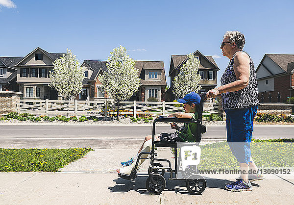 Side view of grandmother pushing grandson on wheelchair on footpath during sunny day