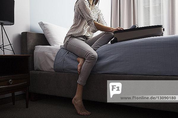 Unterer Teil einer Geschäftsfrau  die im Hotelzimmer Kleidung im Koffer sucht