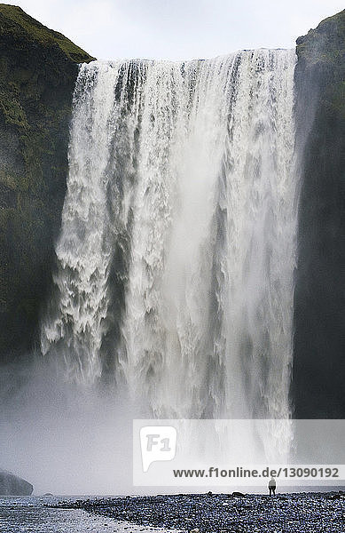 Fernsicht auf einen am Wasserfall stehenden Mann