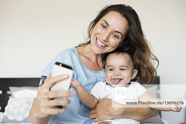 Happy mother taking selfie while sitting with son on bed at home