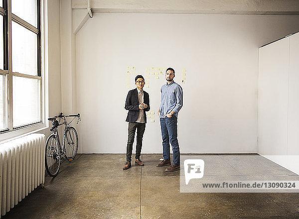 Geschäftsleute stehen im Kreativbüro an weißer Wand