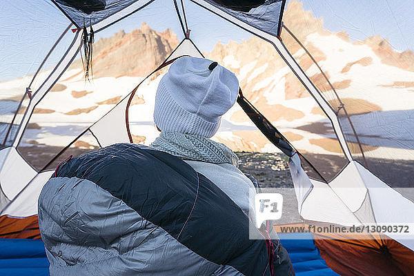 Rückansicht eines Wanderers  der im Zelt sitzt
