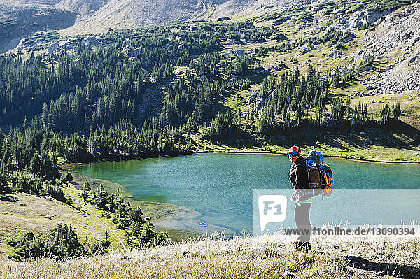 Smiling woman carrying backpack standing against lake in mountain