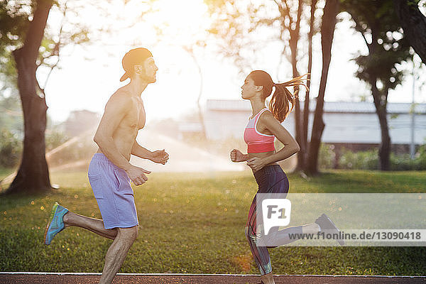 Side view of couple exercising at park on sunny day