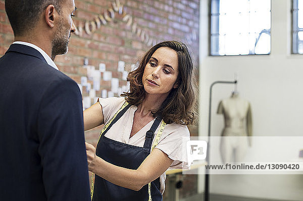 Modedesignerin vermißt Geschäftsmann im Stehen beim Workshop