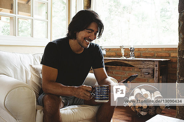 Smiling man using smart phone while sitting on armchair at home