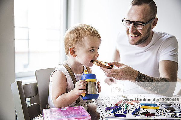 Smiling father feeding cute daughter while drawing at table