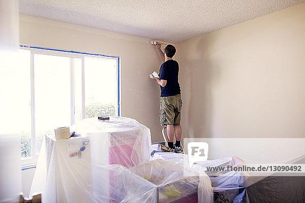 Rückansicht eines Mannes  der eine Wand im Haus malt