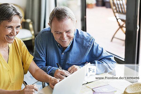 Fröhliches älteres Ehepaar mit Laptop bei der Urlaubsplanung zu Hause