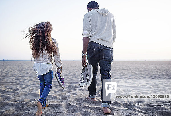 Rear view of father and daughter carrying shoes while walking at beach against clear sky