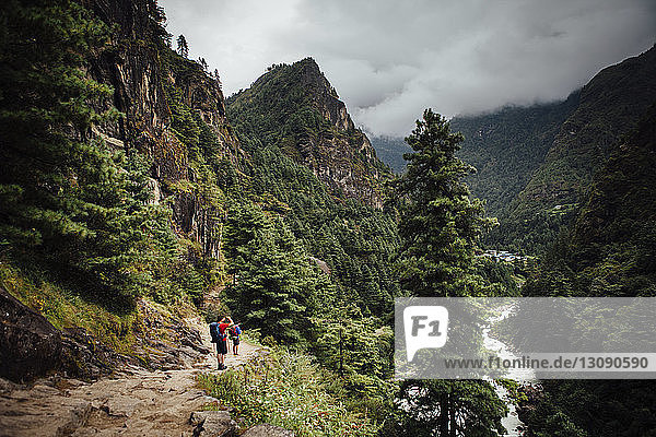 Friends hiking at Sagarmatha National Park against cloudy sky