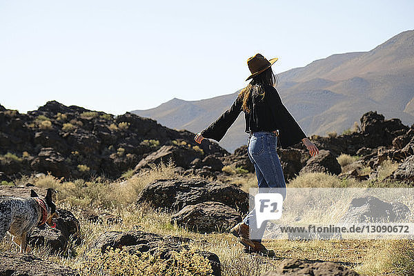 Side view of woman with dog standing on grassy field against clear sky during sunny day