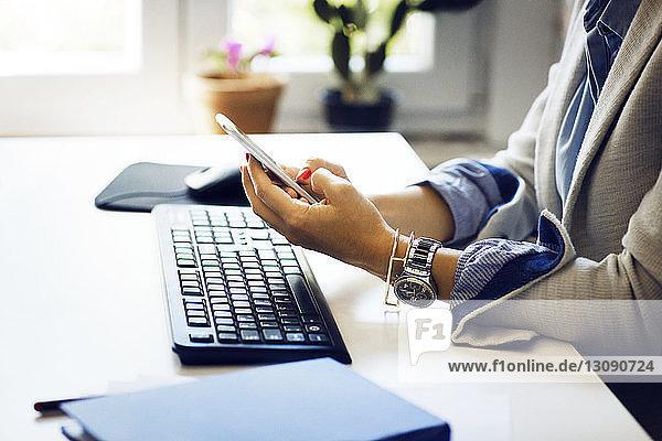 Mittelsektion einer Geschäftsfrau  die bei der Arbeit am Schreibtisch im Büro telefoniert