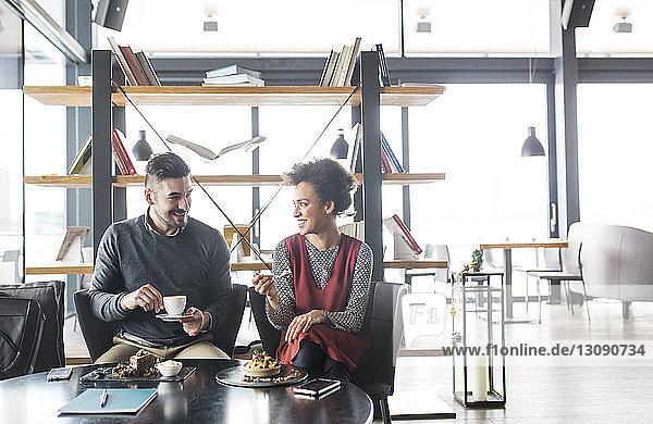 Glückliches Geschäftspaar bei Obst und Kaffee im Cafe