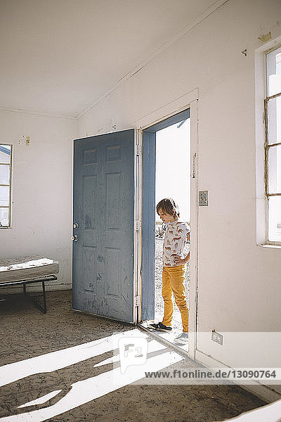 Boy looking at shadow while standing on doorway