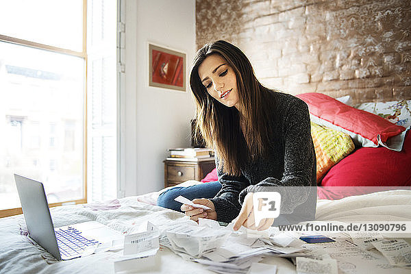Woman reading bills while sitting on bed at home