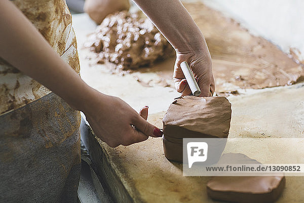 Midsection of female potter making clay on table in workshop