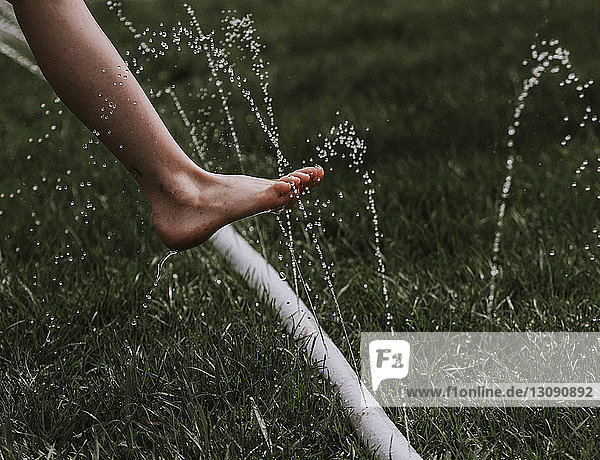 Low section of boy over water spraying garden hose on grassy field at backyard