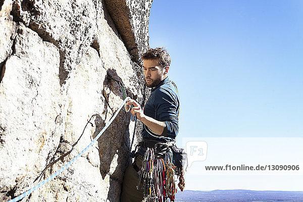 Mann betrachtet Kletterseil beim Klettern am Fels bei klarem Himmel
