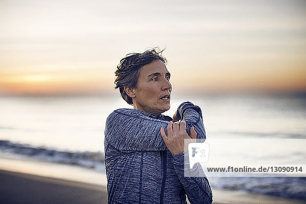 Woman exercising at beach against sky