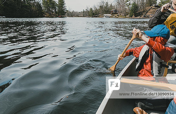 Father and sons sitting in canoe on lake at forest