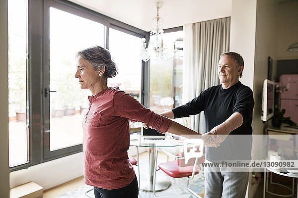 Senior man assisting woman in practicing yoga at home