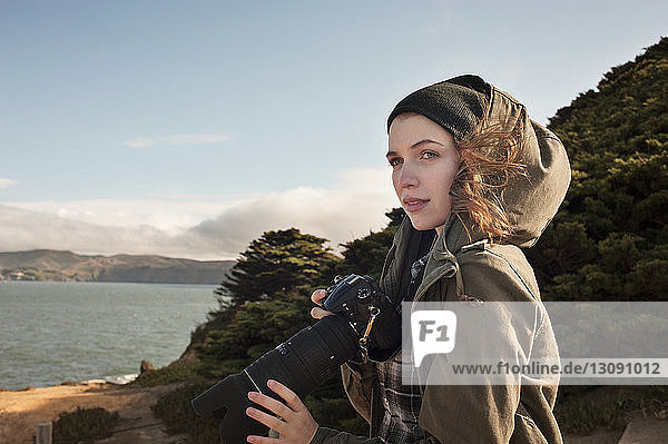 Side view of female photographer looking at view against sky