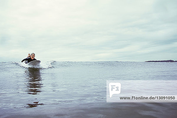 Excited young woman surfing on sea against cloudy sky