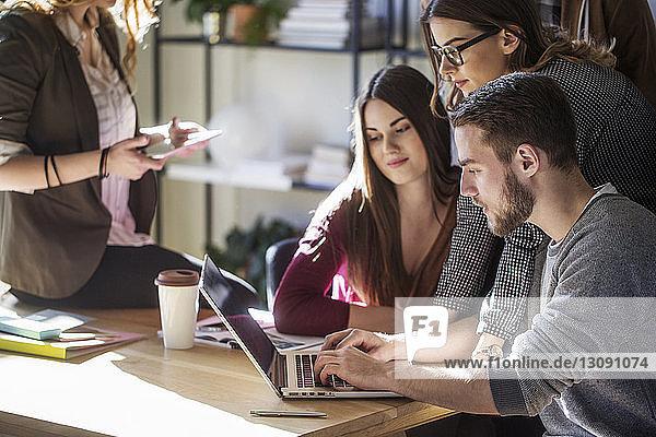 Studenten  die während des Studiums im Klassenzimmer auf einen Laptop schauen