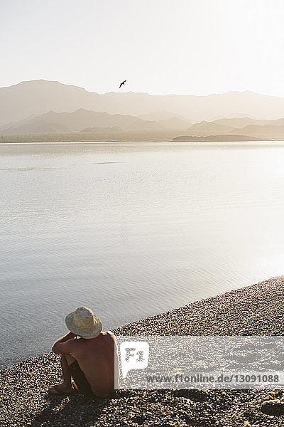 Hochwinkelansicht eines Mannes ohne Hemd  der am Seeufer vor Bergen und klarem Himmel am sonnigen Tag sitzt