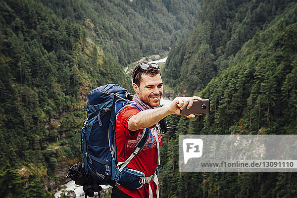 Male hiker taking selfie while standing on mountain at Sagarmatha National Park