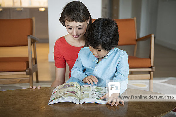 Mother reading book with son at table