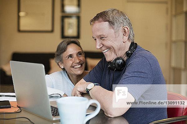 Fröhliches älteres Ehepaar mit Laptop zu Hause
