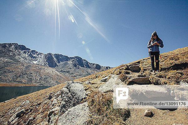 Wanderin benutzt Mobiltelefon  während sie am Berg vor blauem Himmel steht